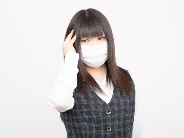 頭が痒くて掻いているマスクをした女性